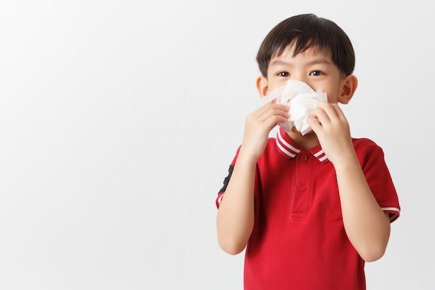 Il piccolo ragazzo asiatico che tiene un tessuto e soffia il suo naso. capretto con rinite fredda.