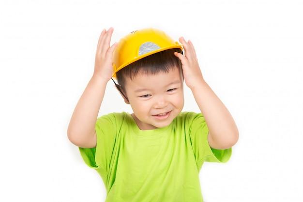 Il piccolo ragazzo asiatico del bambino che gioca i blocchi di legno indossa l'ingegnere del casco