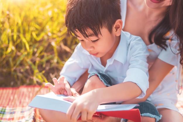 Il piccolo ragazzo asiatico e sua madre che leggono la storia raccolgono i libri al campo del prato. madre e figlio imparano insieme.
