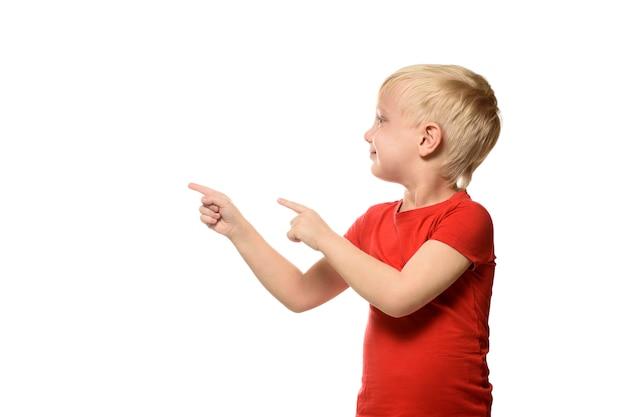 Il piccolo ragazzo biondo sorridente in una camicia rossa sta e mostra i dito indice al lato.