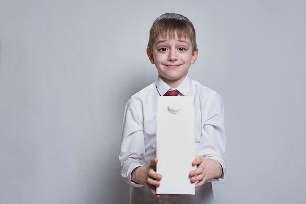Il piccolo ragazzo biondo tiene e mostra un grande pacchetto bianco del cartone. camicia bianca e cravatta rossa.
