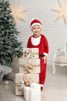 Il piccolo ragazzo sorridente felice in costume del babbo natale tiene il contenitore di regalo di natale bianco