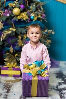 Il piccolo ragazzo sorridente felice tiene il contenitore di regalo di natale.