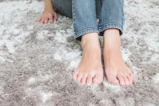 Il piede del primo piano della donna asiatica che si siede sul pavimento grigio del tappeto ha strutturato il fondo in casa