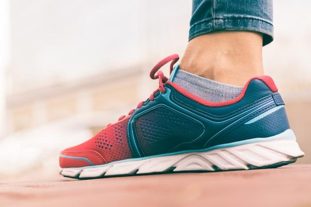 Il piede delle donne in primo piano della scarpa da tennis rossa e blu, tiro di angolo basso