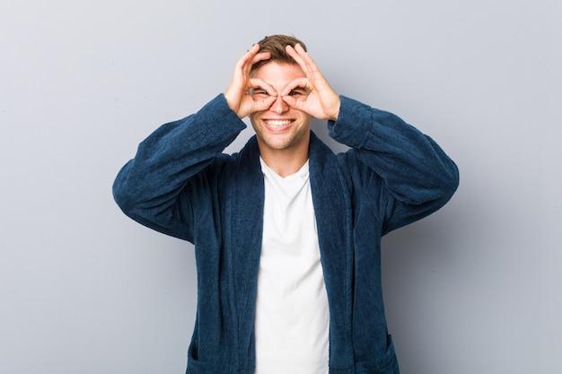 Il pigiama da portare del giovane uomo caucasico che mostra bene firma sopra gli occhi