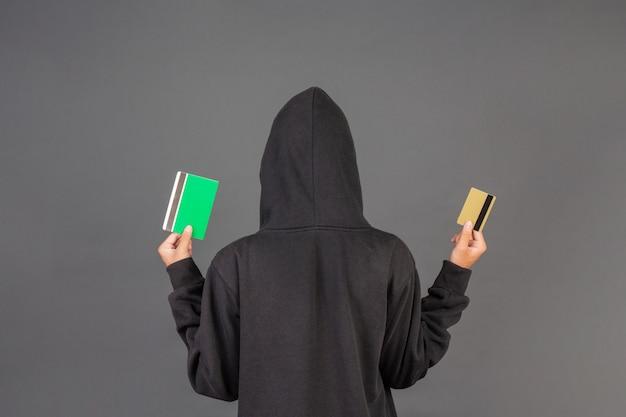 Il pirata informatico sta portando una carta di credito in oro e un libretto di banca