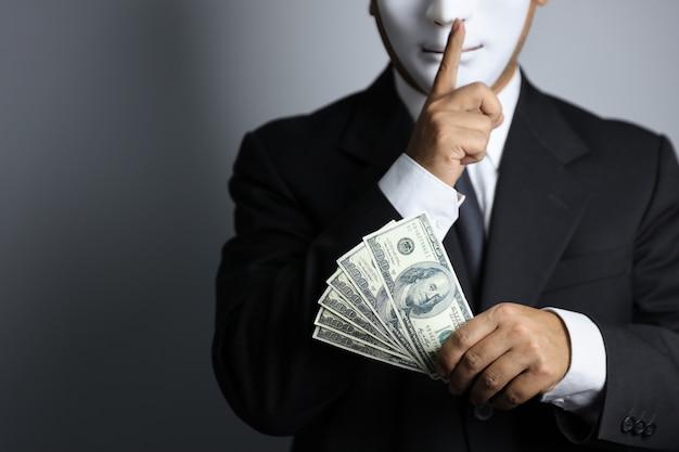 Il politico o l'uomo d'affari che indossa il vestito nero e la maschera bianca mostrano le banconote
