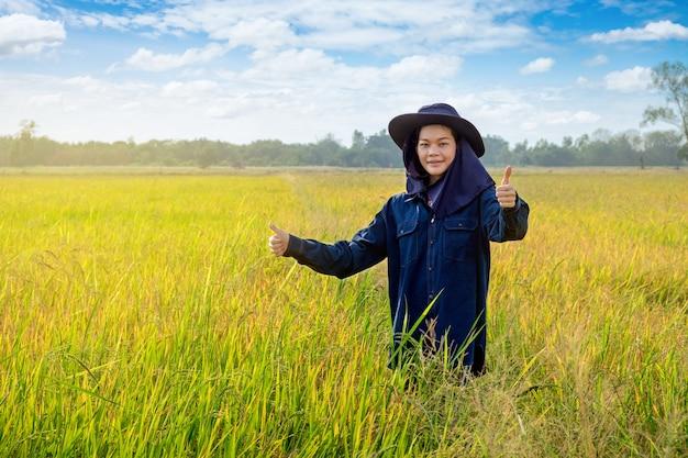 Il pollice femminile asiatico del coltivatore su lavora sul giacimento del riso con il cielo piacevole