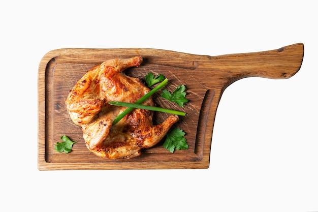 Il pollo appetitoso del tabacco è servito su un tagliere di legno. vista dall'alto isolato su bianco