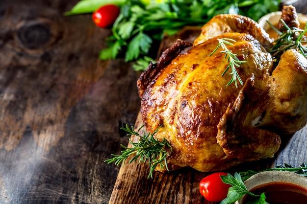 Il pollo arrostito con rosmarino è servito con le salse sul bordo di legno, il fuoco selettivo, spazio della copia