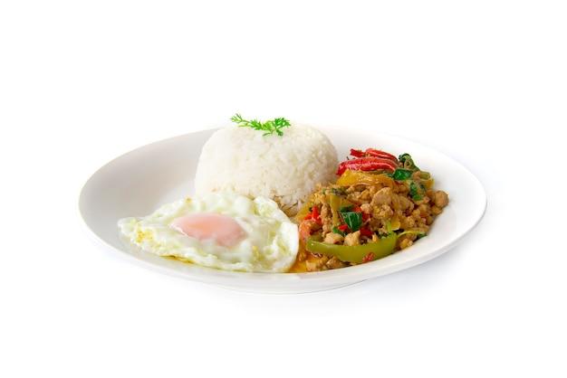 Il pollo e basilico saltati in padella dell'alimento tailandese è servito con riso e l'uovo fritto