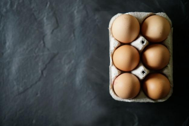Il pollo eggs in scatola di cartone su ardesia con lo spazio del testo