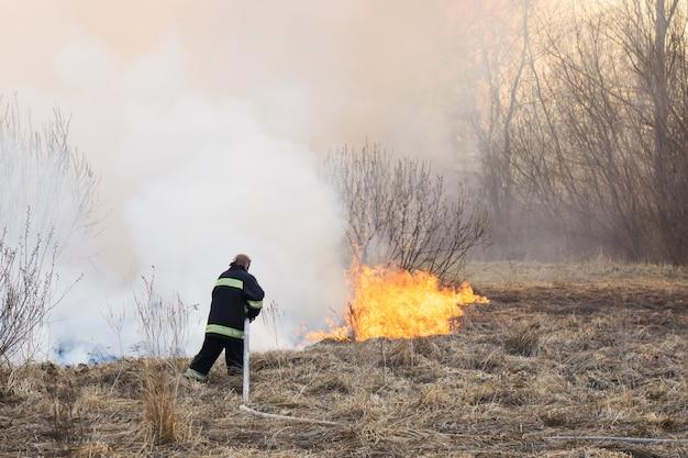 Il pompiere combatte un incendio che si diffonde nell'erba secca e nei cespugli nella palude