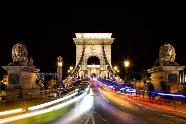 Il ponte a catena di szechenyi con la luce variopinta trascina di notte nella città di budapest, ungheria