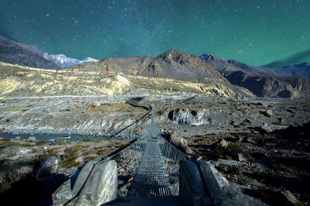 Il ponte sospeso con le bandiere buddisti di preghiera sul circuito di annapurna trek nel nepal. terra di shangri-la.