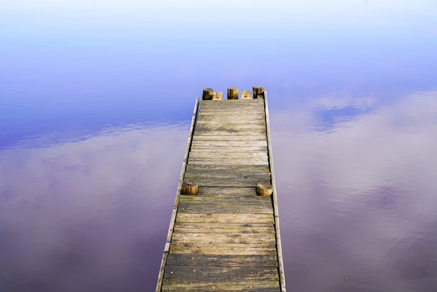 Il pontone di legno sul lago sembra fluttuare nel cielo con il riflesso