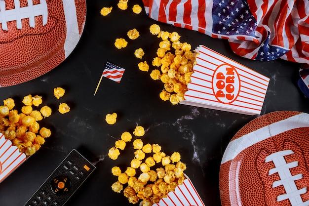 Il popcorn giallo in scatole a strisce si è rovesciato sulla superficie nera con il telecomando e la piastra di football americano