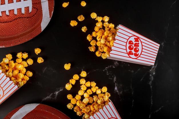 Il popcorn giallo in scatole a strisce si è rovesciato sulla tavola nera con il piatto di football americano