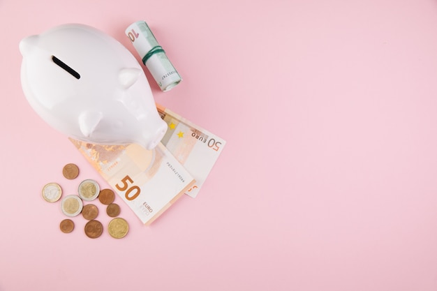 Il porcellino salvadanaio salva la moneta ed i soldi, fondo di scrittorio rosa, vista superiore