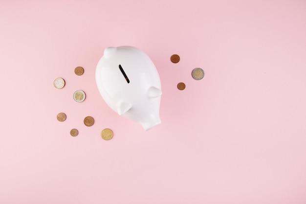 Il porcellino salvadanaio salva la moneta, fondo di scrittorio rosa, vista superiore