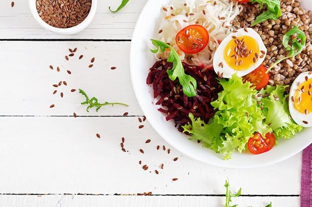 Il porridge di grano saraceno buddha ciotole con barbabietola, cavolo, uova sode e pomodoro fresco sulla tavola bianca. colazione salutare. vista dall'alto