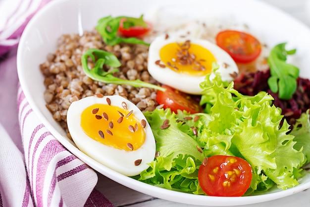 Il porridge di grano saraceno buddha ciotole con barbabietola, cavolo, uova sode e pomodoro fresco sulla tavola bianca. colazione salutare.
