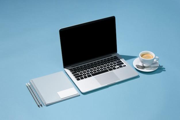 Il portatile, penne, telefono, nota con schermo bianco sul tavolo