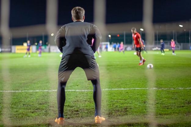 Il portiere prende la palla quando è sulla difensiva in porta durante una partita di calcio