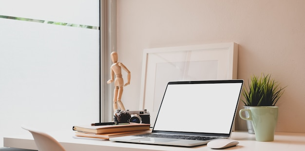 Il posto di lavoro comodo del fotografo con il computer portatile dello schermo in bianco