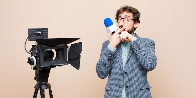 Il presentatore televisivo sembra serio e scontento di entrambe le dita incrociate in segno di rifiuto, chiedendo silenzio