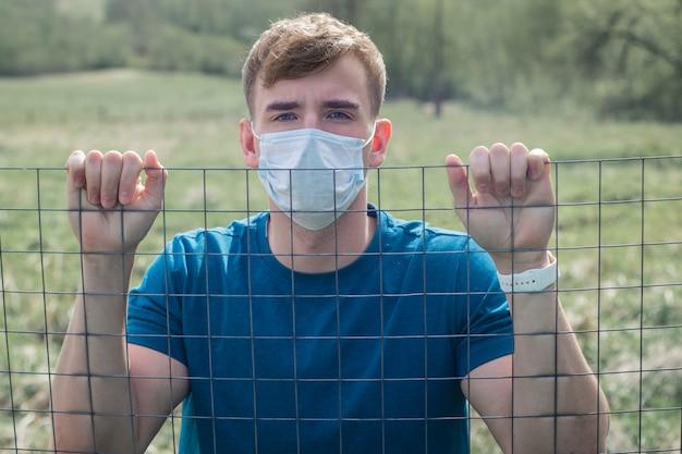 Il prigioniero del tipo nella maschera protettiva sul suo fronte ha isolato la condizione dietro le barre, grata. limitazione della libertà. autoisolamento, infezione da virus dell'epidemia di coronavirus. covid19. giovane isolato in prigione