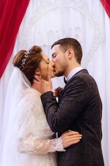Il primo bacio nel ruolo di marito e moglie sullo sfondo