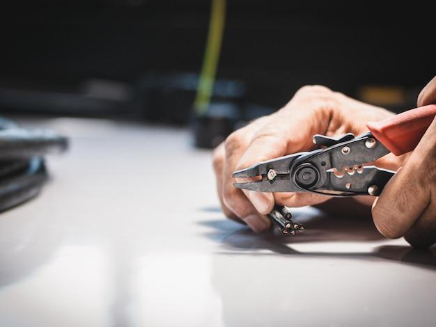 Il primo piano alla mano di un elettricista sta usando le pinze di spogliatura elettriche nelle applicazioni industriali.
