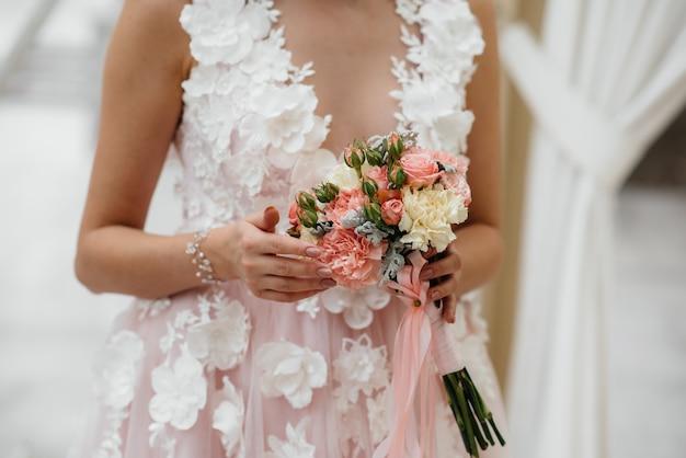 Il primo piano bello e sofisticato del mazzo di nozze tiene la sposa in sue mani. bouquet da sposa