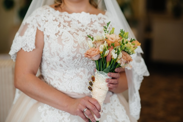 Il primo piano bello e sofisticato del mazzo di nozze tiene la sposa in sue mani. bouquet da sposa.