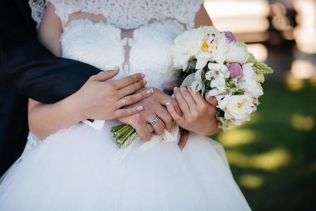 Il primo piano bello e sofisticato del mazzo di nozze tiene la sposa in sue mani vicino allo sposo. bouquet da sposa e anelli