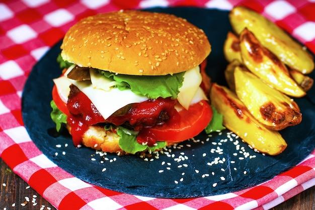 Il primo piano degli hamburger di manzo fatti casa con lattuga è servito sul tagliere e sul tovagliolo di pietra