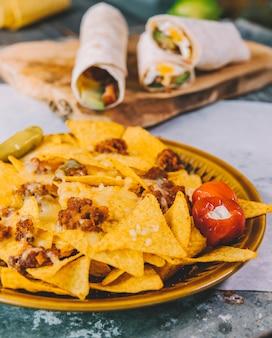Il primo piano dei nachos messicani deliziosi scheggia in piatto