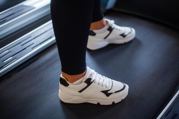 Il primo piano dei piedi della giovane donna in abiti sportivi sta correndo su una pedana mobile in palestra
