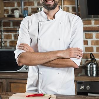 Il primo piano del cuoco unico maschio con il braccio ha attraversato la condizione dietro il contatore di cucina