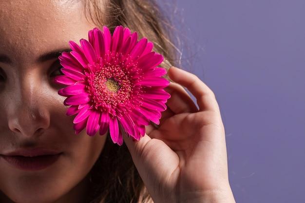 Il primo piano del fiore ha tenuto dallo spazio della copia e della donna