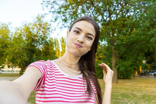Il primo piano del fronte d'avanguardia della ragazza sta facendo la foto del selfie