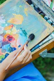 Il primo piano del pennello in mani della donna che mescolano le pitture sulla tavolozza all'aperto