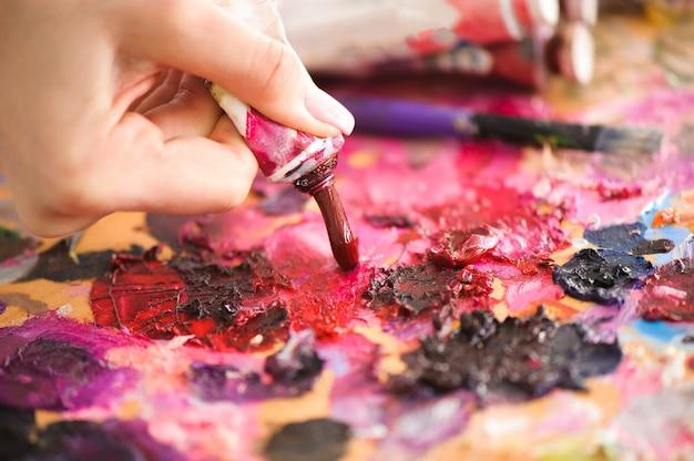 Il primo piano del pennello in mani della donna che mescolano le pitture sulla tavolozza