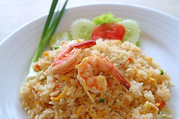 Il primo piano del riso fritto di stile tailandese con gambero o khao pad goong è servito sul piatto bianco ceramico