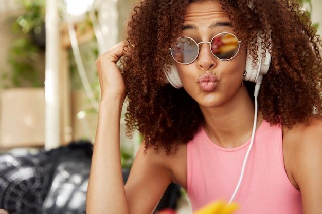 Il primo piano del volto di una donna dall'aspetto piacevole e stiloso in tonalità ha un'acconciatura africana, le labbra arrotondate, ha un'espressione divertente, gode della musica preferita o dell'audio in cuffia sul sito web della radio. persone e concetto di stile