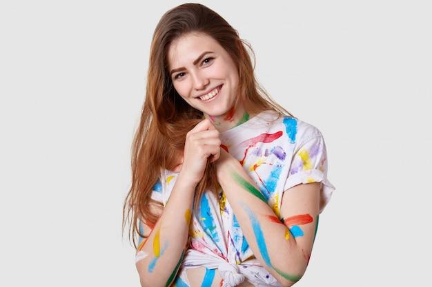 Il primo piano del volto di una giovane modella femmina positiva tiene le mani unite, sorride dolcemente, indossa una maglietta macchiata casual, si diverte a dipingere