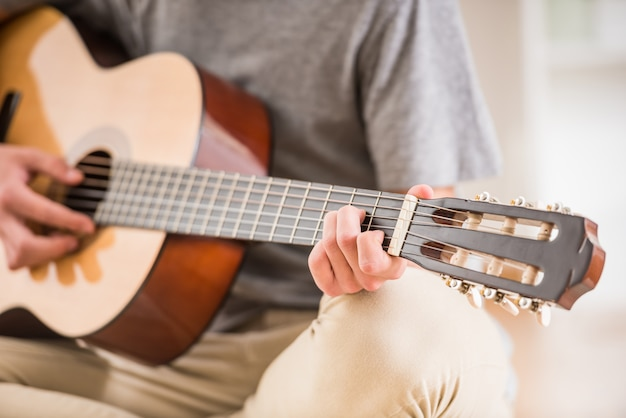 Il primo piano dell'adolescente è seduto a casa e suonare la chitarra.