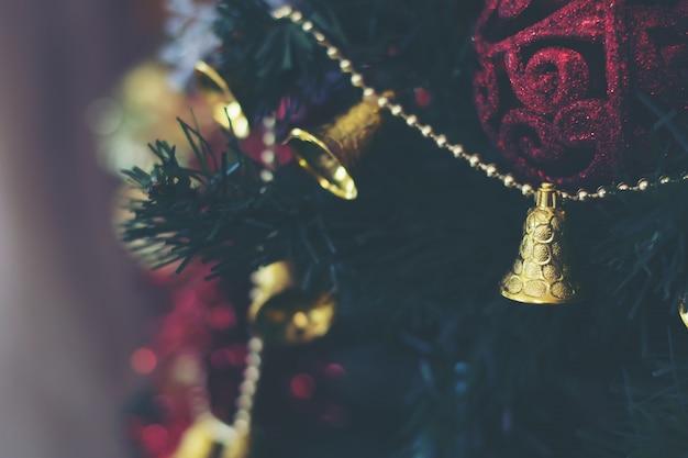 Il primo piano dell'albero di natale con le palle e la campana decorano sopra